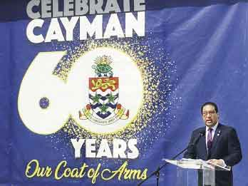 Cayman Islands Premier Alden McLaughlin speaking in front of a coat of arms anniversary banner