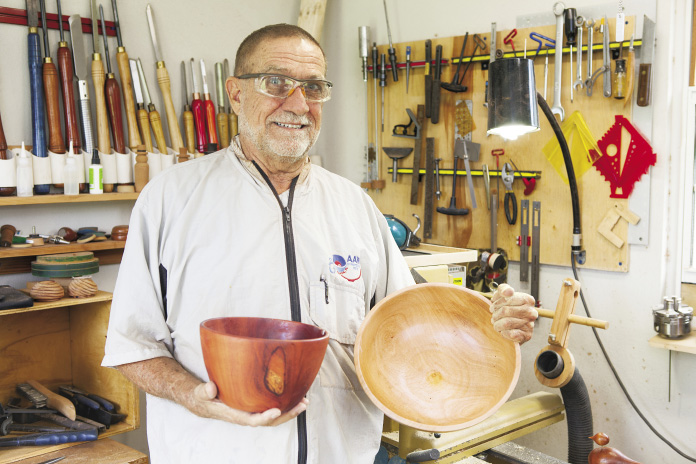 Len Layman in his workshop holding two wooden bowls.