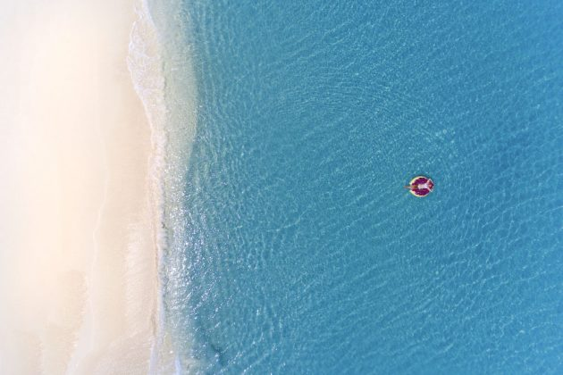 Aerial view of a woman floating in the clear waters just off a Cayman beach.