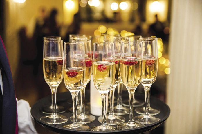 Champagne flutes filled with bubbly and a strawberry on a tray.